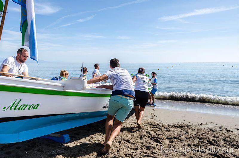 """empujando una embarcación """"jábega"""" de madera pintada de blanco, azul y verde, hacia el mar"""