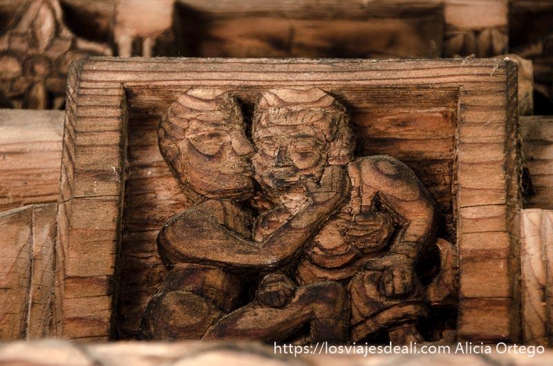 relieve en madera de una pareja dándose un beso en templo cerca de manali