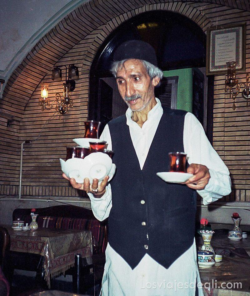 camarero con camisa blanca larga y chaleco negro a juego con gorrito negro, portando una docena de vasos llenos de té con sus platos, en una sola mano.