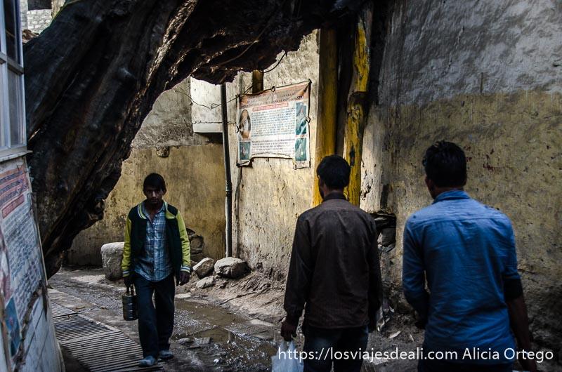chicos andando por una calle de Leh que parece en ruinas a primera hora de la mañana