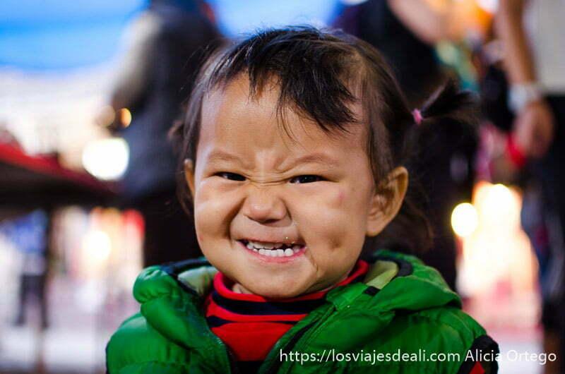 niña tibetana con dos coletas riéndose en mercado de leh