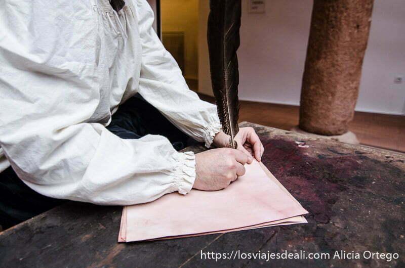 manos de hombre vestido de época escribiendo en papel con una pluma como cervantes alcázar de san juan