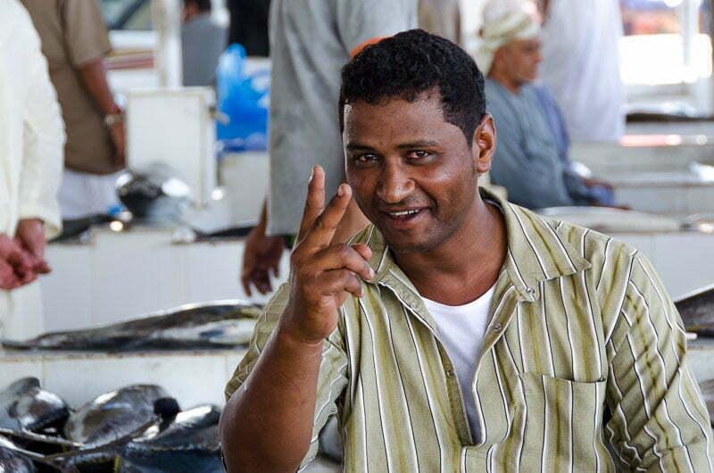 chico haciendo V de victoria junto a su puesto de pescado en mercado de pescado en omán