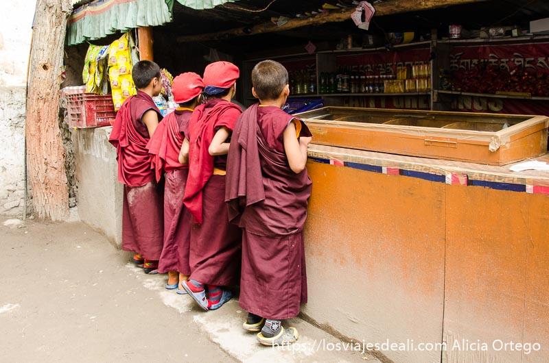 niños monje con sus hábitos rojos comprando chuches en la tienda del monasterio valle del indo