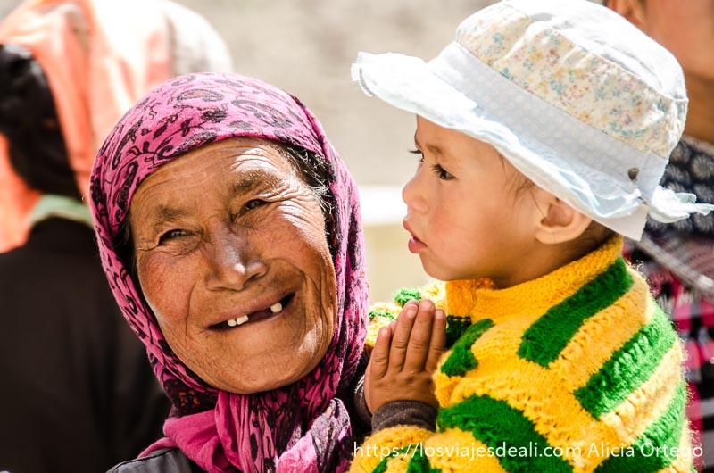 anciana con tres dientes se ríe con su nieto en brazos valle del indo