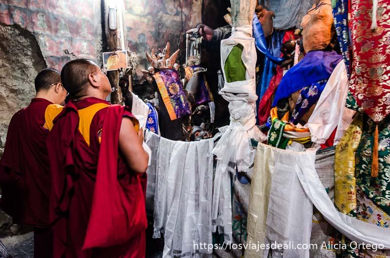dos monjes rezando ante estatuas cubiertas de telas blancas valle del indo