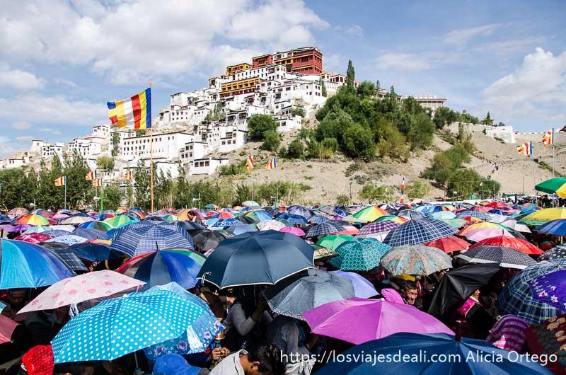 cientos de paraguas de colores y el monasterio de thiksey al fondo sobre la montaña una conferencia del dalai lama