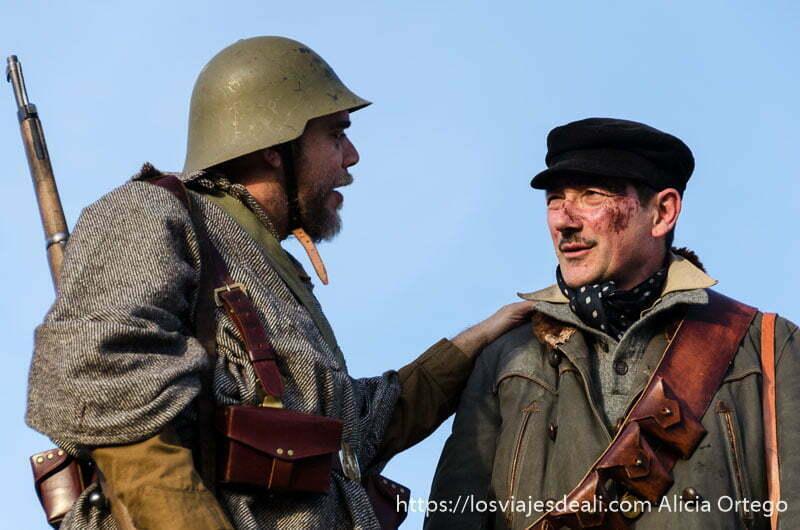 soldado con casco y fusil al hombro saluda a otro con gorra y herida en la cara en recreación batalla del jarama