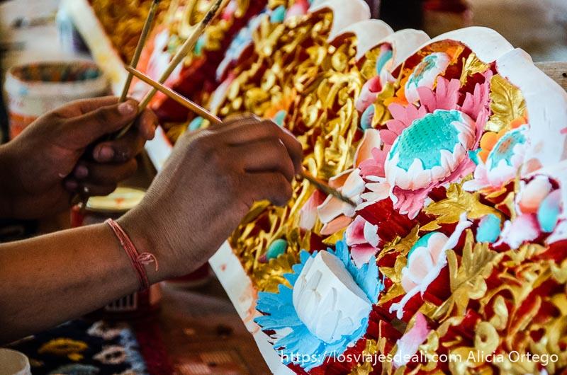 manos pintando madera labrada de colorines trekking cerca de leh