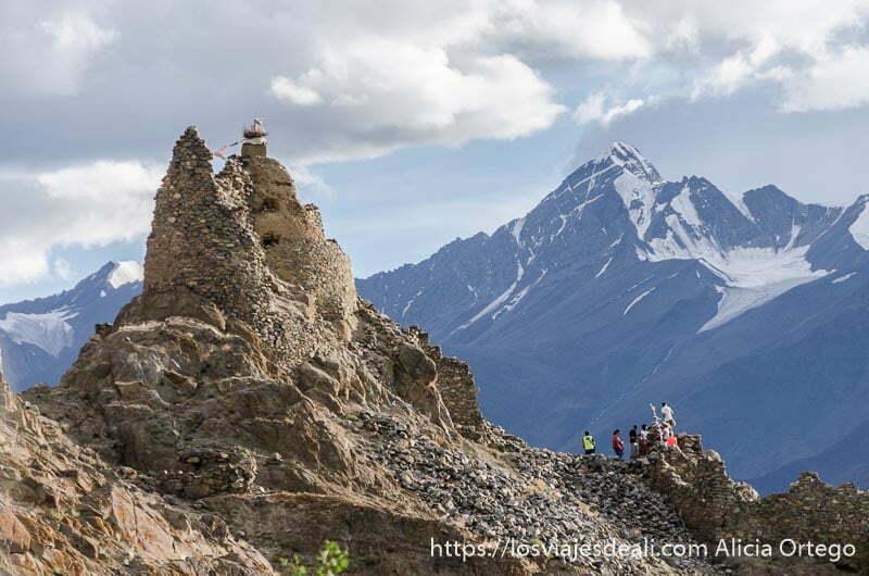 grupo de viajeros junto a monasterio budista y al fondo pico alto del himalaya en trekking cerca de leh