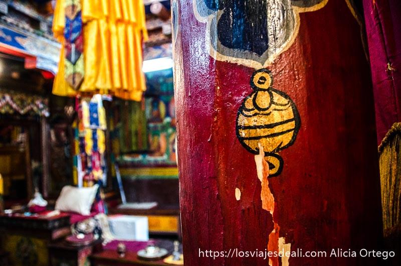 columna del templo pintada de rojo con dibujo de molino de oración trekking cerca de leh