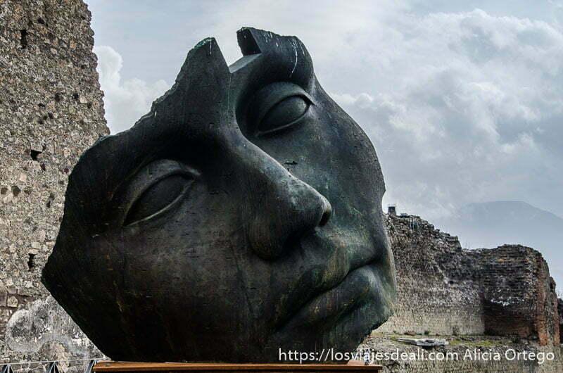 escultura de bronce que es la cara de un hombre visita a pompeya