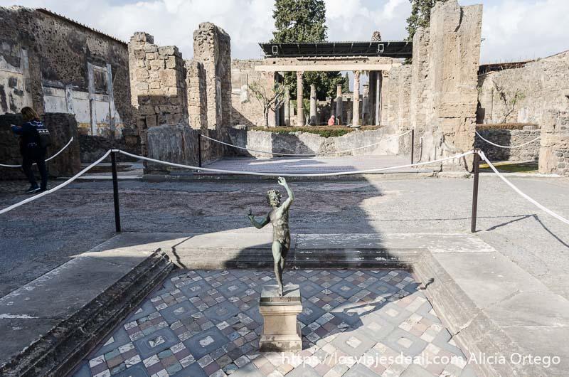 patio con fuente y figura de un fauno de bronce en el centro
