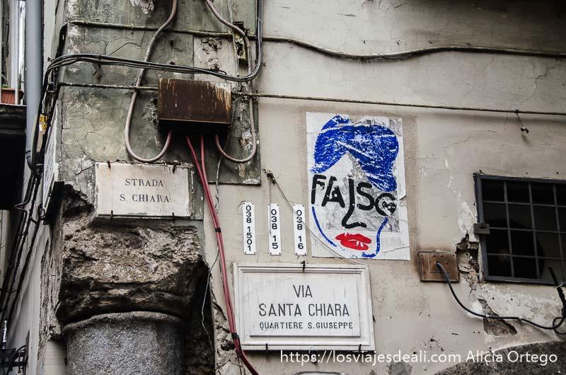 carteles grafitis y cables en una esquina de nápoles