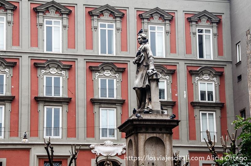 estatua con palomas en la cabeza y ventanas de palazzo detrás paseos por nápoles