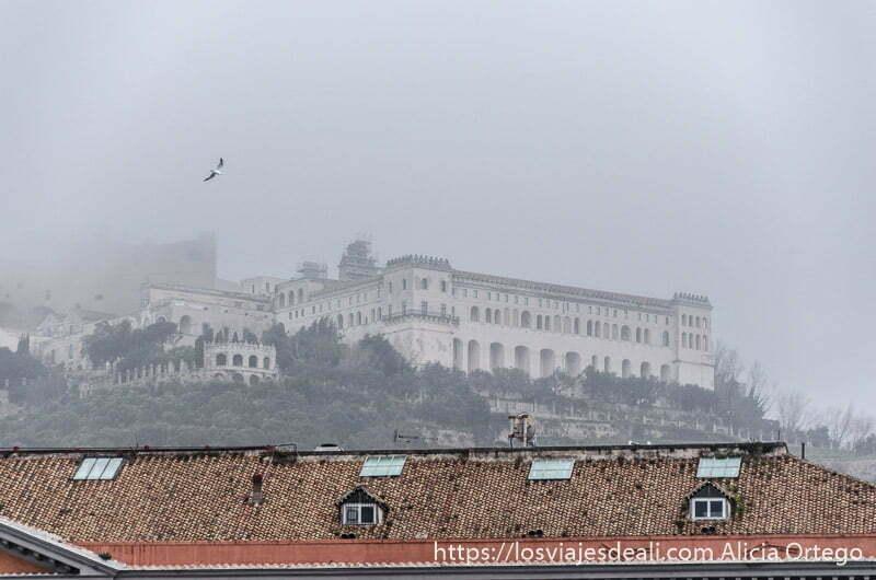 castillo entre la niebla y tejados rojos debajo paseos por nápoles