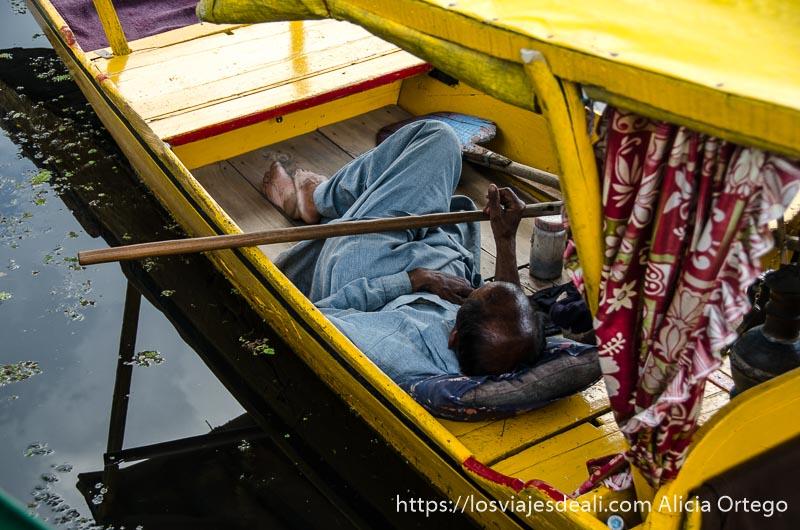 barquero tumbado en su barca en el lago dal srinagar