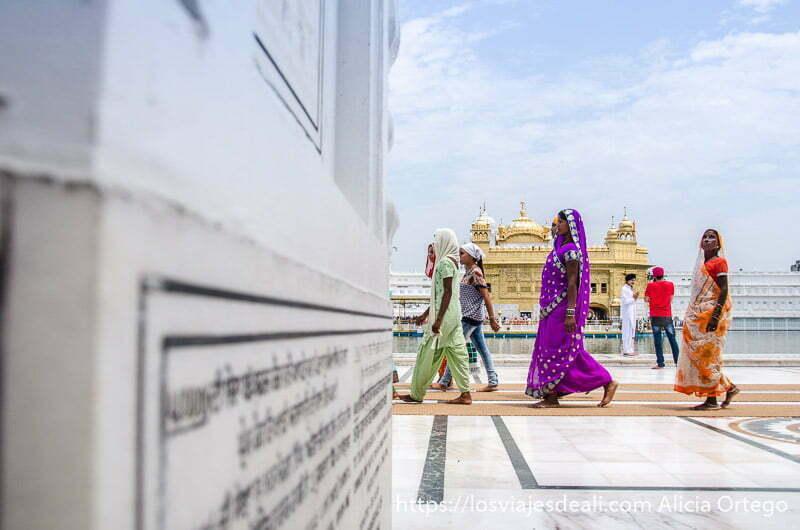mujeres con saris de colores andando en el templo dorado de los sijs