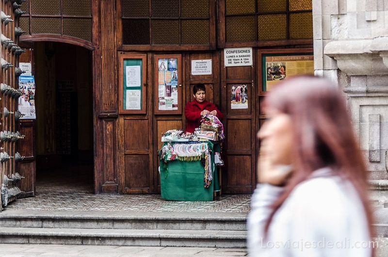 mujer pasando delante de la puerta de una iglesia donde hay otra mujer con un puesto de venta de recuerdos