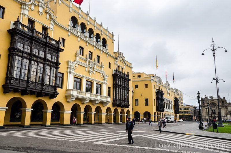 casas coloniales con grandes balcones de madera oscura y pintadas de amarillo en la plaza de armas de lima