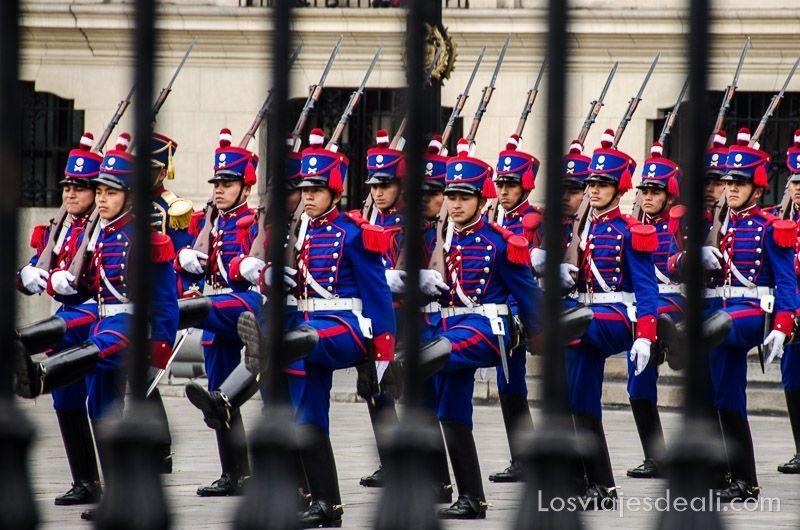 soldados vestidos de uniforme azul y rojo marchando en formación