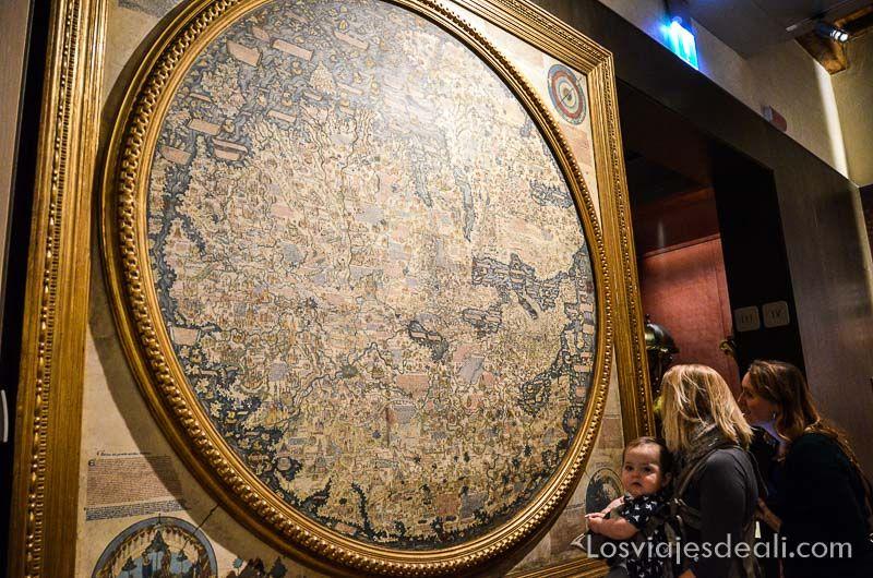 Gran mapamundi antiguo y dos chicas con un bebé observándolo