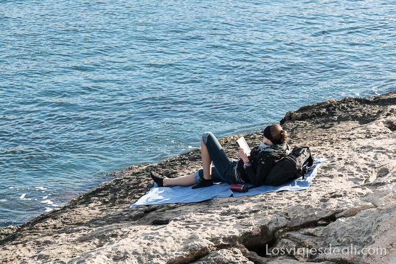 chica joven tumbada sobre rocas apoyada en la mochila leyendo con el mar de frente