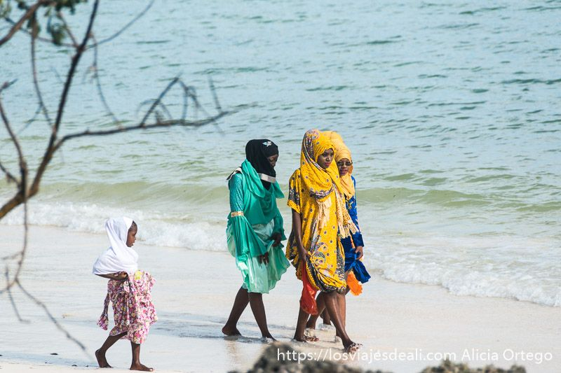 mujeres musulmanas con vestidos de colores y cabeza tapada con velo pasean por una playa de zanzíbar 8 de marzo