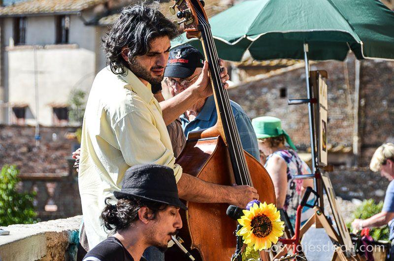 músicos jóvenes con un violonchelo y clarinete tocando con turistas alrededor