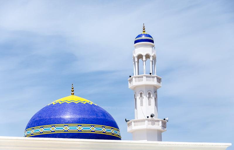 cúpula con azulejos azules y amarillos y torre del moecín en Muscat