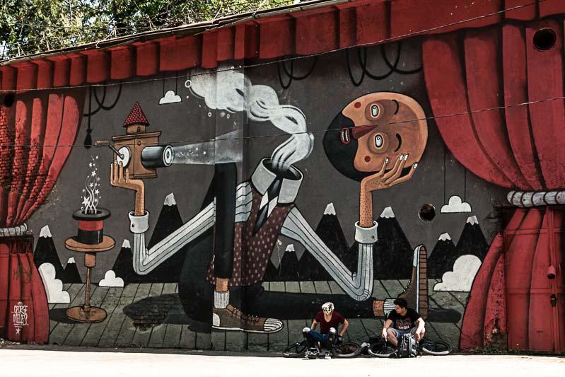 mural de arte callejero en brasov con dos ciclistas sentados junto a él