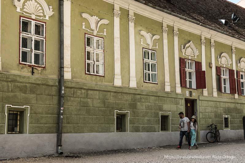 palacio barroco pintado de verde con una pareja pasando delante