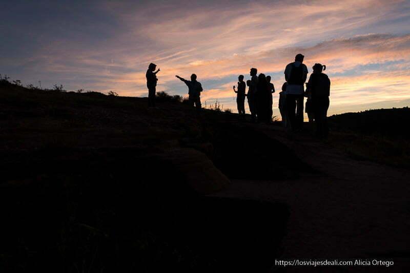grupo de visitantes a contraluz en tiermes con horizonte lleno de nubes rosadas