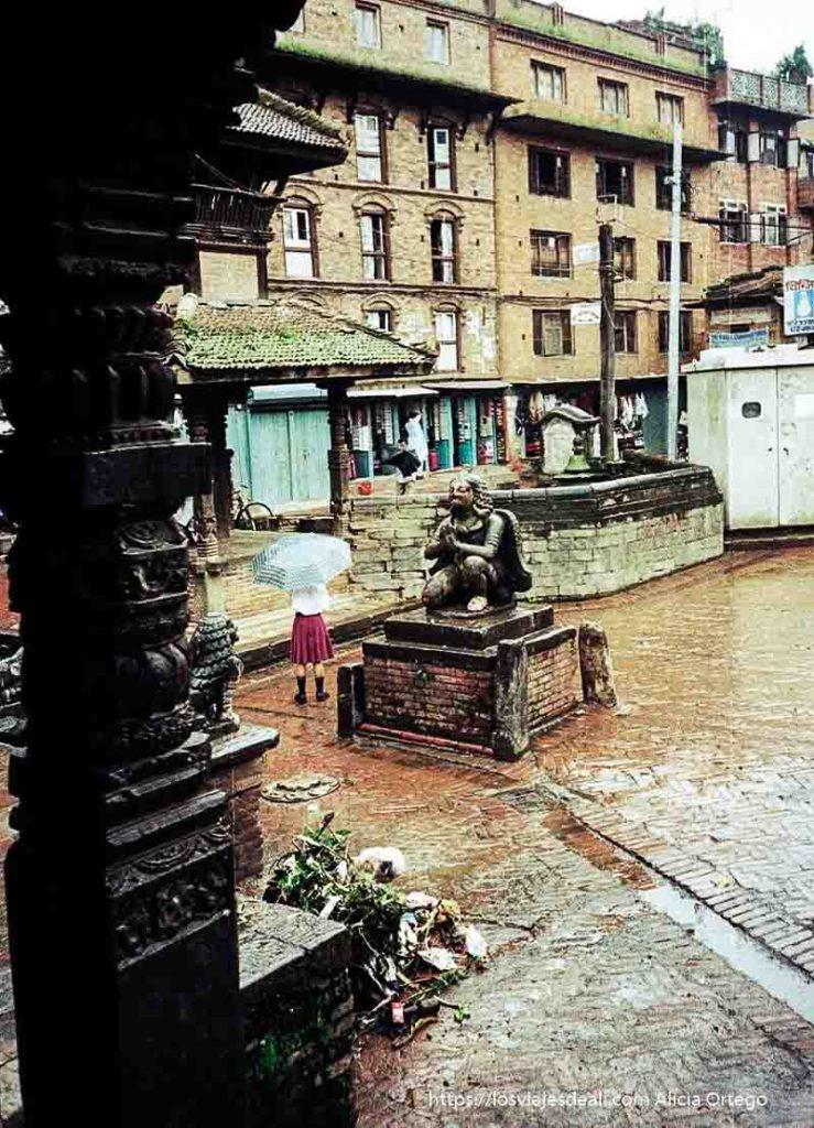 estatua de dios en plaza de baktapur con niña con paraguas al lado nepal