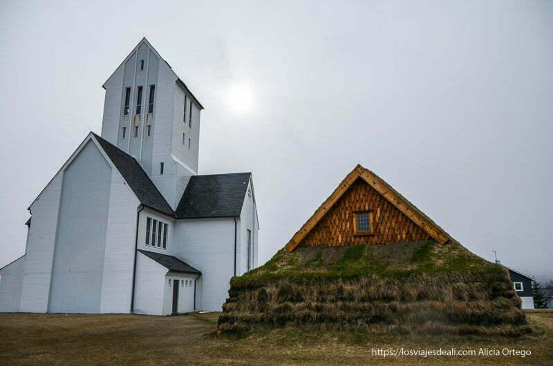 iglesia de madera blanca junto a casa tradicional islandesa cubierta de hierba
