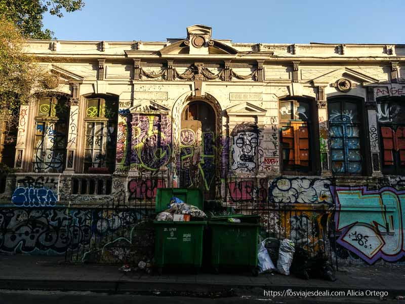 palacete lleno de grafittis con cubos de basura delante en barrio yungay de santiago de chile