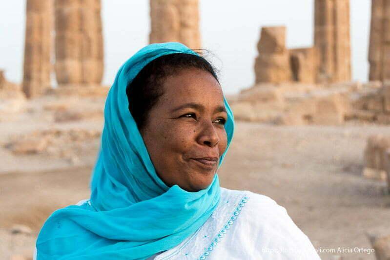 retrato de shadia con velo azul y las columnas de soleb detrás gentes de sudán