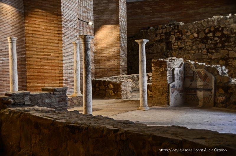 ruinas de casas romanas con columnas y una pared con frescos en los sótanos del museo de arte romano de mérida