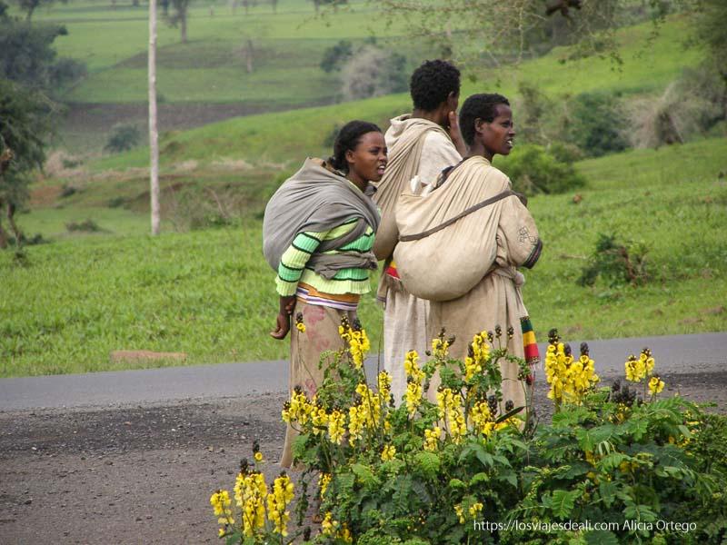 mujeres con bebés a la espalda de camino a gondar