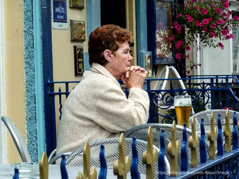 mujer mayor pensativa tomando una pinta kilkenny