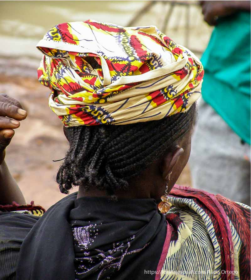 mujer de espaldas con peinado de trencitas y telas de colores en mopti