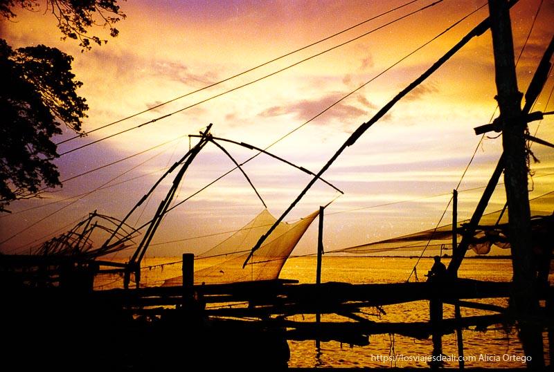 redes de pesca en atardecer de colores intensos en kerala