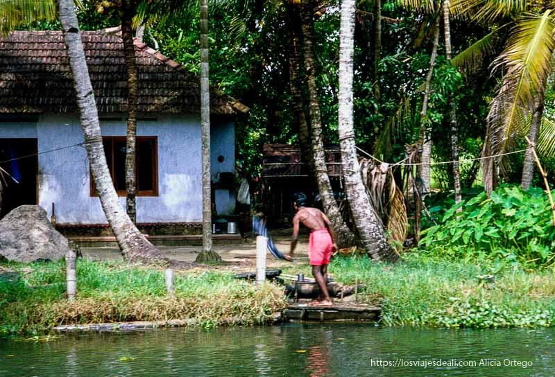 un hombre lavando ropa en un canal de kerala