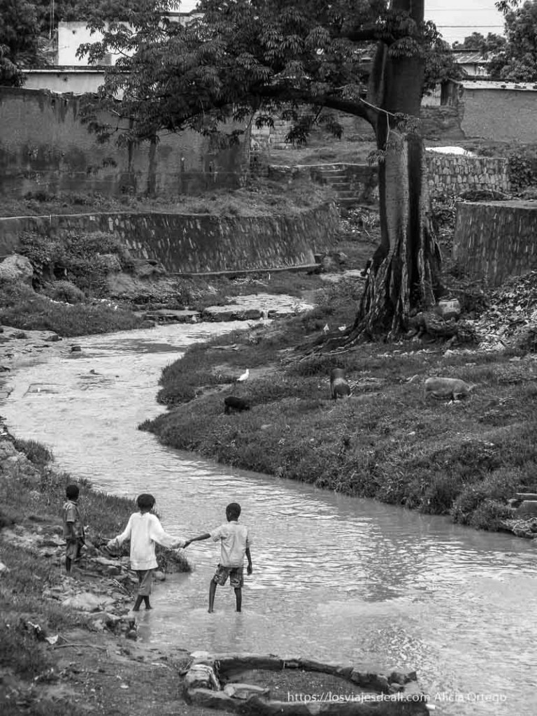 curva de río con tres niños cogiéndose de la mano en bobo dioulasso