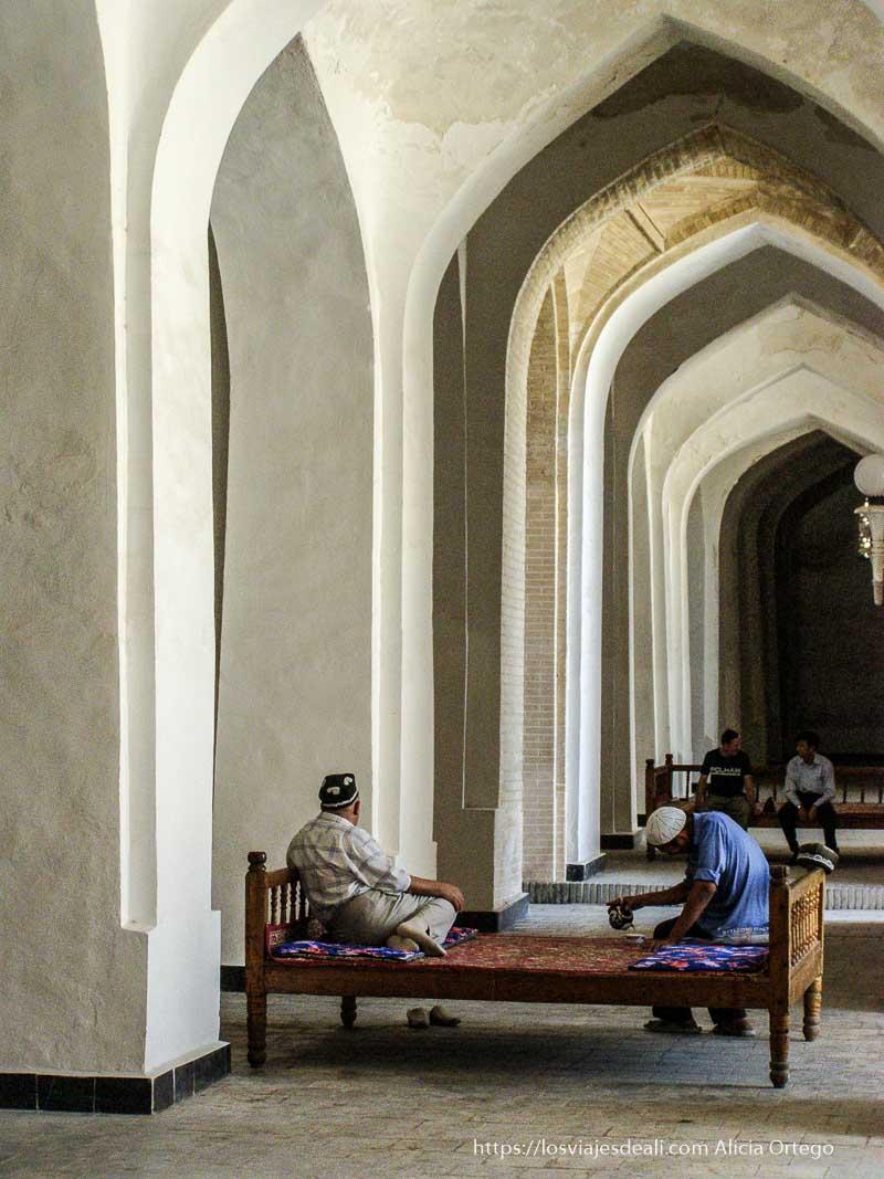 hombres tomando té bajo arcos encalados en bukhara