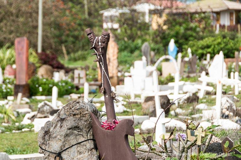 tumba con escultura rapa nui con dos cabezas y un collar de conchas en el cementerio de hanga roa