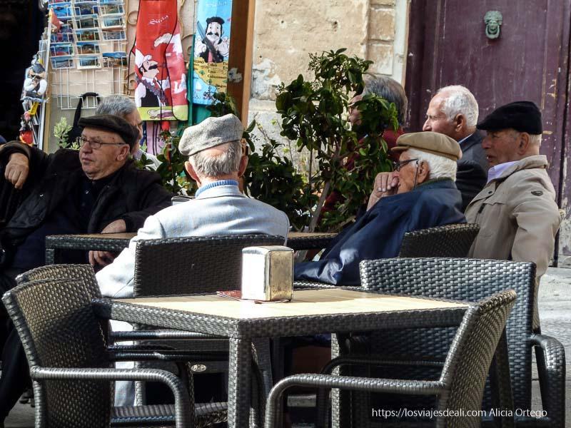ancianos sicilianoscon sus gorras sentados en una terraza en cefalú