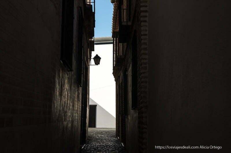 callejón con farola recortándose en fachada blanca del fondo centro de málaga