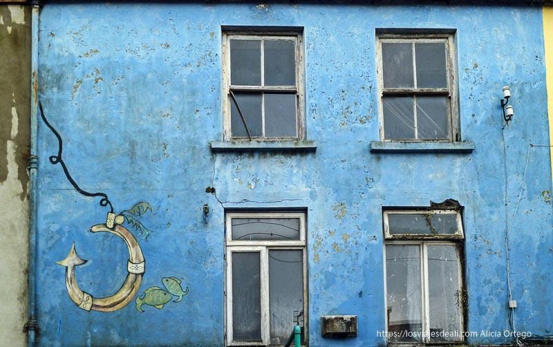fachada azul con dibujo de anzuelo y peces en dingle