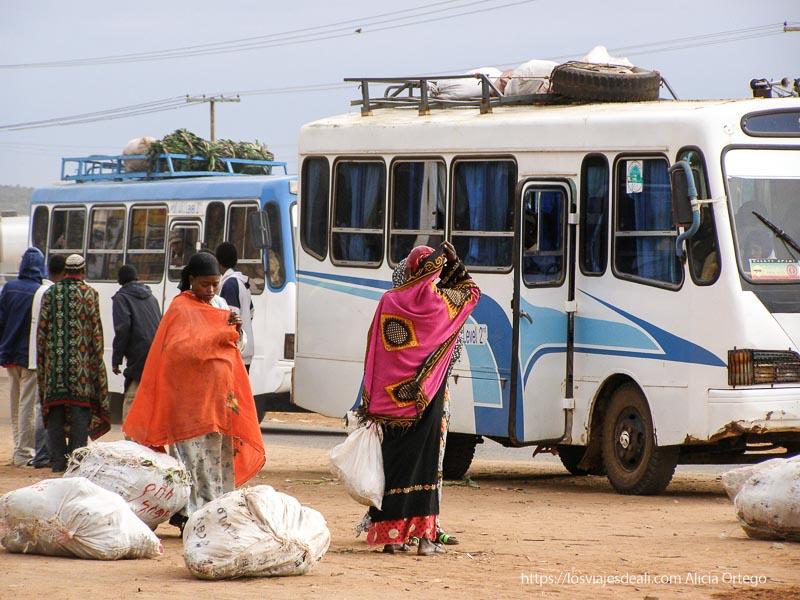 parada de autobús hay mujeres con telas de colores y sacos el sod